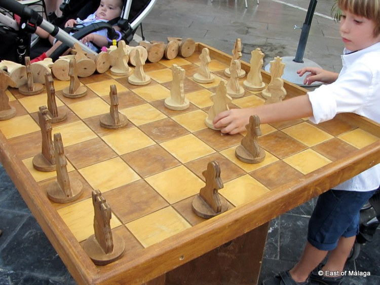 Child plays on wooden chess table at medieval market in Torrox pueblo
